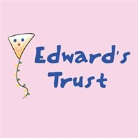 "Pink background with navy blue text saying ""Edward's Trust"" next to a kite with a smiling face painted on."