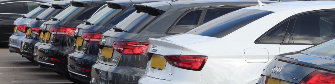 A row of new Audi cars parked in a row, waiting to be sold.