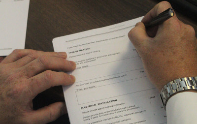 Dave Johnston's hands as he fills out a risk overview document.