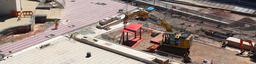 A shot from above of a construction site. There is a digger poised to bite in to the ground.