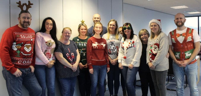 The staff of Johnston Park McAndrew in Christmas jumpers and Christmas deely boppers smiling.
