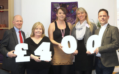 "A picture of Mat McSwiggan and Trish Parr standing with representatives from Edwards Trust holding the numbers and symbols that make up ""£400""."