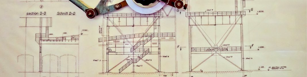 A picture of an engineers diagram with a drawing implement hanging above it.
