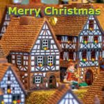 """A close up of traditional clay houses that are often made as a Christmas decoration. TThe words """"Merry Christmas!"""" floating above it."""