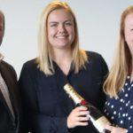 A photo of David Johnston and Sarah Cooksey standing on either side of one of their ex-apprentices after she has achieved her most recent CII qualification. Sarah is handing Amanda a bottle of champagne.